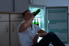 Пиво человека выпивая в кухне Стоковые Фото