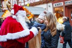 有母亲的小小孩女孩在圣诞节市场上 免版税库存照片