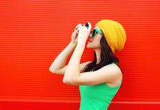 塑造相当穿有照相机的凉快的女孩五颜六色的衣裳 免版税图库摄影