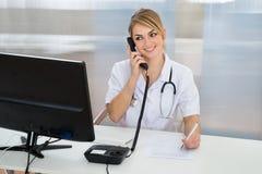 女性医生谈话在电话 库存图片