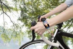 骑自行车的妇女递佩带的健康传感器巧妙的手表 免版税库存图片