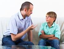 父亲和儿子谈论严肃 图库摄影