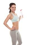 运动的从一个瓶的女孩饮用水在锻炼以后,健身训练,隔绝在白色背景 免版税图库摄影