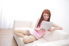 使用在沙发的愉快的妇女片剂个人计算机 免版税图库摄影