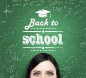 女孩和词的前额:'回到学校'在绿色黑板被写 库存照片
