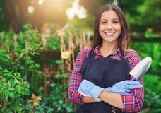 在她的植物中的微笑的年轻托儿所所有者 免版税库存图片