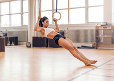 做在体操圆环的年轻人适合的妇女引体向上 免版税库存照片