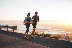 跑步及早在早晨的年轻夫妇 免版税库存图片