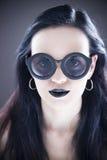 在太阳镜的美丽的妇女时装模特儿画象有黑嘴唇和耳环的 创造性的发型和组成 免版税库存图片