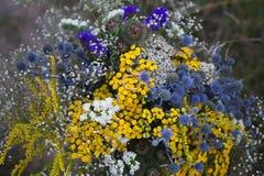 在明亮的蓝色和黄色花,婚礼,提案,生活方式概念花束的两个婚戒  免版税库存照片