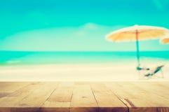 在被弄脏的蓝色海和白色沙子海滩背景的木台式 免版税库存图片