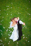 站立在绿草的愉快的婚礼夫妇 免版税库存图片