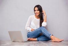快乐的妇女坐与膝上型计算机的地板 库存照片