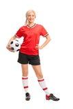 拿着球的女性足球运动员 库存照片