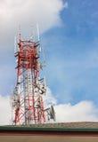 电信塔、屋顶和天空多云背景 免版税图库摄影