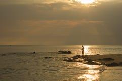 有太阳在海水和海滩的射线亮光在早晨海和多云天空的风景  免版税图库摄影