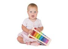 一件桃红色礼服的小女孩弹钢琴 免版税图库摄影