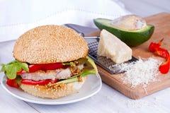 Самонаведите сваренный бургер с индюком, авокадоом, салатом, луками, красным перцем паприки на плюшке семени сезама Стоковая Фотография RF
