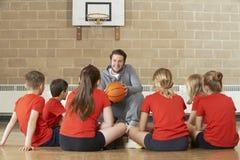 Тренер давая беседу команды к баскетбольной команде начальной школы Стоковое Изображение RF