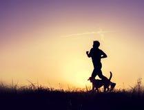 有狗剪影的赛跑者在日落 库存照片