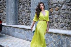 美好的性感的深色的妇女步行丝绸礼服党街道 免版税库存照片