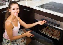 在家烹调意大利薄饼的少妇 免版税库存照片