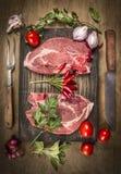 两与肉刀子和叉子的猪肉牛排,新调味料和香料在黑暗的土气木背景,顶视图 库存照片