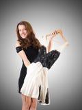 Молодая женщина пробуя новую одежду против градиента Стоковое Изображение