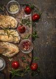 鲜美烤鸡内圆角用草本、香料、调味料和蕃茄在葡萄酒毁坏的板在土气木背景,上面 库存图片