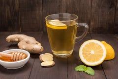 杯姜茶用柠檬和蜂蜜在木背景 免版税库存图片