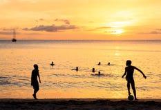 踢在日落的儿童的剪影足球在塔拉法尔海滩 库存照片