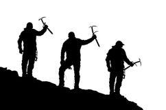 三个登山人黑剪影有冰斧的在手中 免版税库存照片