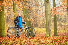 愉快的活跃妇女骑马自行车在秋天公园 图库摄影