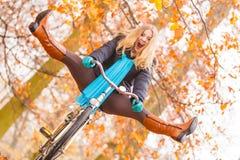 活跃妇女有乐趣骑马自行车在秋天公园 免版税库存图片