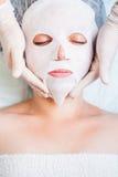 放松在温泉沙龙的妇女应用白色面罩 免版税库存照片