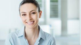 摆在办公室的美丽的微笑的女商人 免版税库存图片