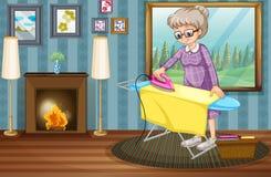 老妇人电烙的衣裳在房子里 免版税库存图片
