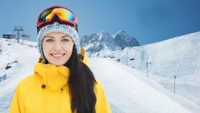 滑雪风镜的愉快的少妇在山 免版税库存照片
