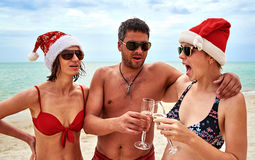 英俊的人和两个美丽的女孩圣诞节圣诞老人帽子的在 库存照片