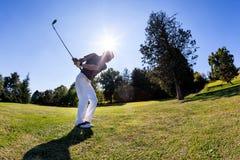 高尔夫球体育:高尔夫球运动员击中从航路的射击 免版税图库摄影