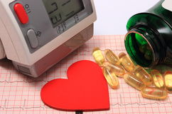 Μορφή καρδιών, όργανο ελέγχου πίεσης του αίματος και ταμπλέτες στο ηλεκτροκαρδιογράφημα Στοκ Φωτογραφία