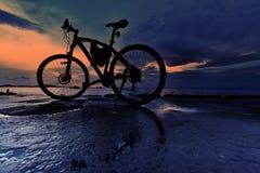 自行车停车处剪影在海旁边的有日落天空的 免版税库存照片
