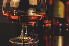 一口威士忌酒在典雅的典型的科涅克白兰地玻璃的白兰地酒在瓶前面在背景中 图库摄影