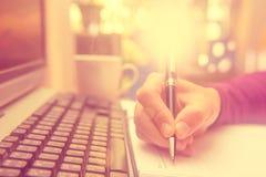供以人员举行在笔记本的手笔文字 免版税库存图片