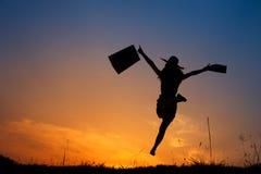 拿着购物袋的愉快的妇女跳跃在日落剪影 库存照片
