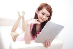 使用在沙发的愉快的妇女片剂个人计算机 库存图片