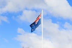 反对美丽的白色云彩的新西兰旗子在蓝天 免版税库存照片