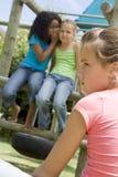 朋友女孩操场二耳语的年轻人 免版税库存照片