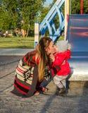 毛线衣的年轻美丽的母亲是使用和乘坐在与她的小小女儿的摇摆一个红色夹克和帽子的在 库存照片