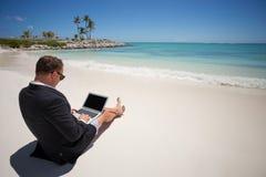 使用片剂计算机的商人在海滩 免版税库存照片